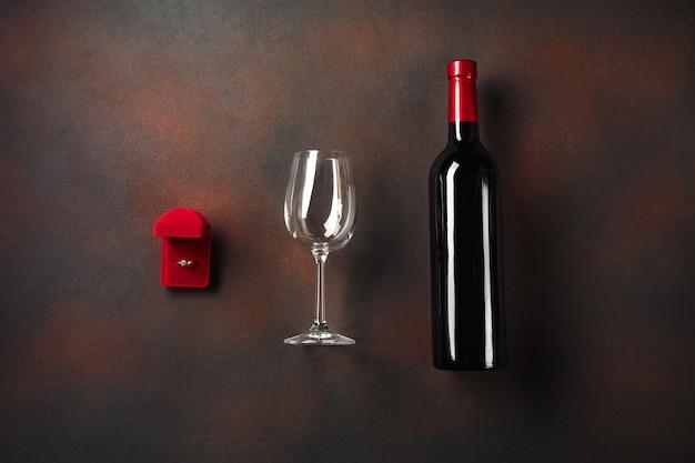 San valentino con una bottiglia di vino e un bicchiere e un anello di fidanzamento.