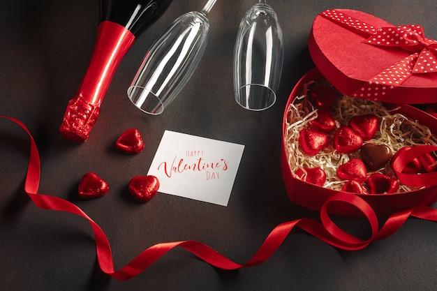 San valentino con una scatola di cioccolatini a forma di cuore con una bottiglia di spumante con bicchieri e una nota