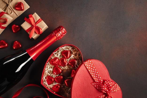San valentino con una scatola di cioccolatini aperta sotto forma di abbondanti doni e spumante. vista dall'alto con lo spazio della copia.