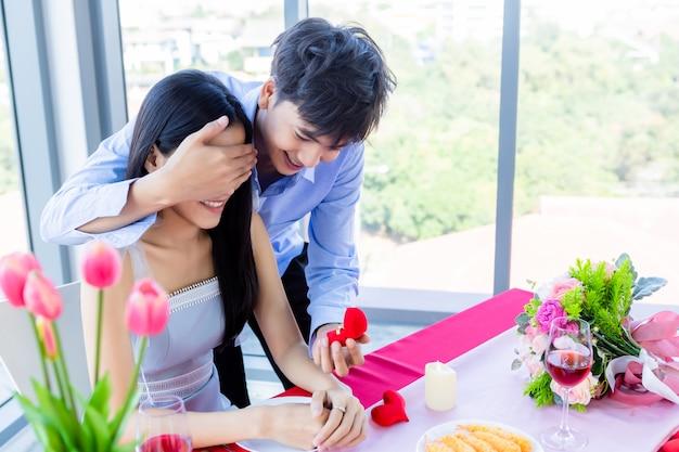 San valentino e asiatiche giovani felici coppie dolci concetto, asiatiche un uomo con anello di fidanzamento che presenta una proposta di matrimonio a una donna dopo pranzo in un ristorante, sposa e sposo piani di matrimonio