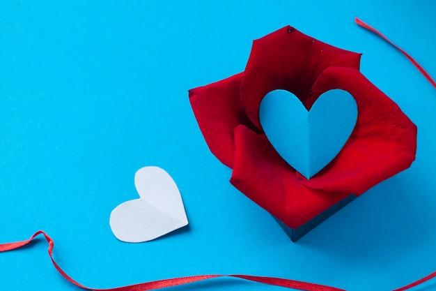 San valentino e l'ottavo marzo, petali di rosa e cuore in scatola su sfondo blu