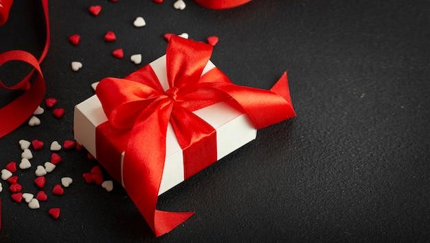 San valentino, festa della mamma, 8 marzo. confezione regalo con fiocco rosso e nastro rosso, cuori rossi. copia spazio.