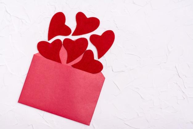 San valentino. i cuori di feltro rosso volano fuori da una busta rossa aperta. copia spazio