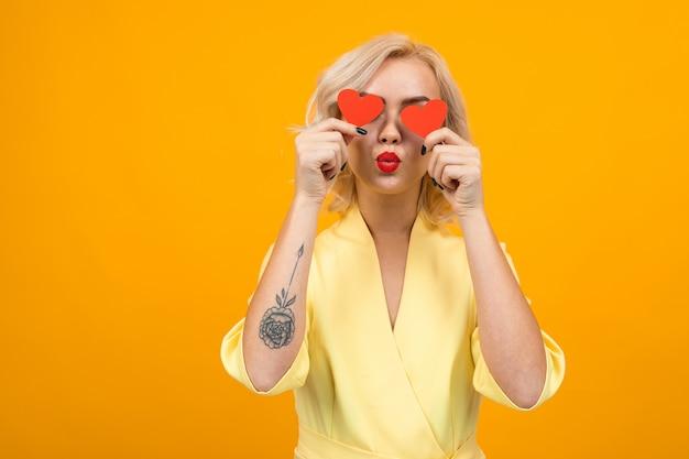 San valentino . la ragazza bionda tiene le carte del biglietto di s. valentino vicino agli occhi su giallo