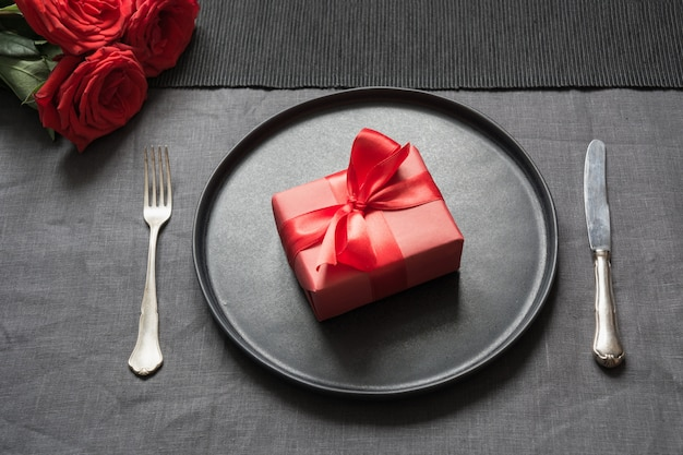 San valentino o cena di compleanno. regolazione della tabella di eleganza con la rosa rossa sulla tovaglia di tela nera.
