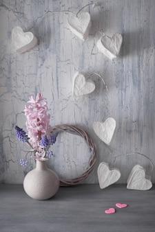 San valentino o festa di primavera, vaso con fiori di giacinto e ghirlanda di luci con cuori di carta