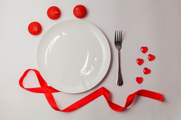 San valentino piatto laici. piatto bianco vuoto sul tavolo con estate rossa, cuori e candele e forcella.