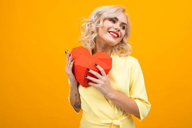 San valentino . ritratto di una ragazza bionda felice con il trucco con un cuore rosso fatto di carta su un giallo con copyspace