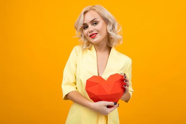San valentino . ritratto di una ragazza bionda felice sexy con rossetto rosso con un cuore rosso fatto di carta su un giallo