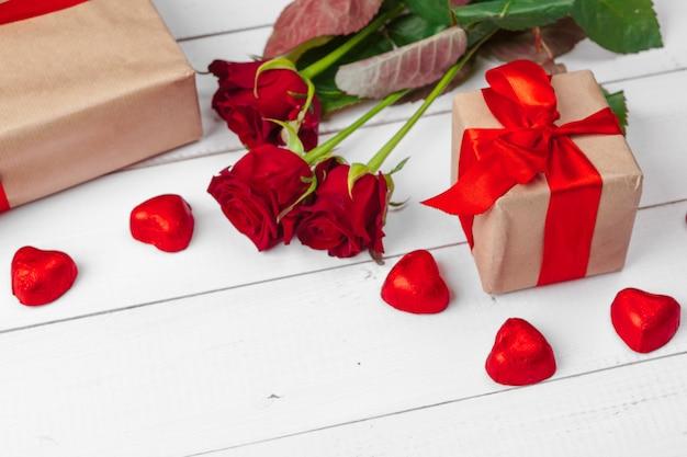 San valentino. rose rosse e contenitore di regalo sulla tavola di legno