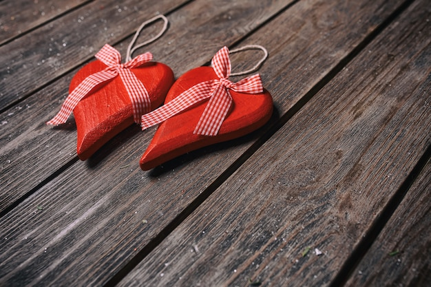 San valentino sfondo. coppie dei cuori rossi con il nastro a quadretti su fondo di legno.