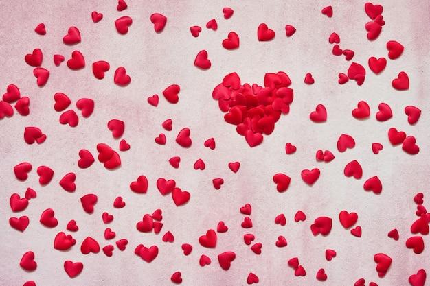 San valentino sfondo cuori rossi su sfondo rosa. copia spazio, vista dall'alto.