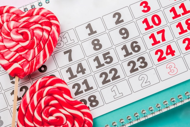 San valentino sfondo rosa chiaro concetto di biglietto di auguri due lecca-lecca cuore rosso o caramelle dolci su bastoni e calendario