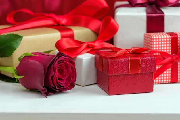 San valentino sfondo rosso con rose e scatola regalo.