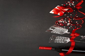 San valentino sullo sfondo. vino, cuori, regalo, bicchieri su cemento scuro