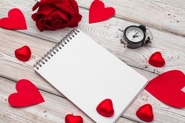 San valentino. taccuino in bianco vuoto, contenitore di regalo, fiori, vista dall'alto. spazio libero per il testo