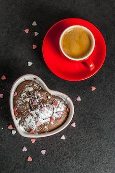 San valentino, tazza di caffè rossa e torta tazza di cioccolato o brownie con zucchero a velo e spruzza a forma di cuore dolce, nero, copyspace vista dall'alto
