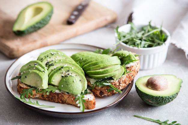 Sana colazione con avocado e delizioso toast integrale. fette di avocado su pane tostato con spezie.