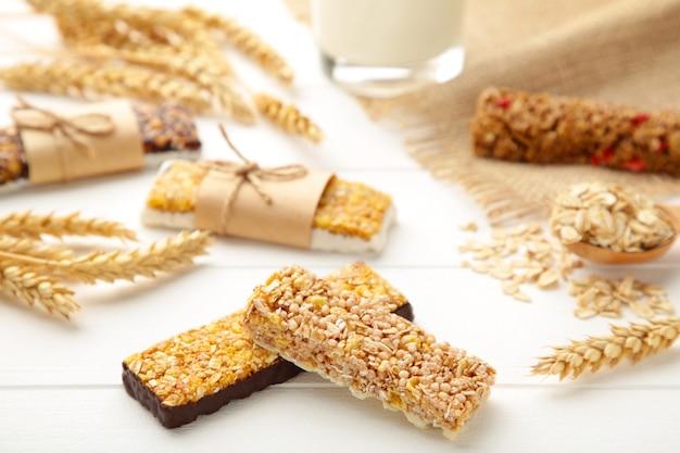 Sana colazione con barrette di cereali e latte sul tavolo di legno bianco.