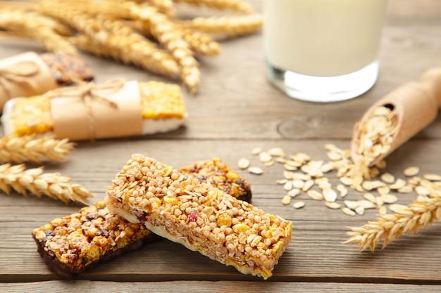 Sana colazione con barrette di cereali e latte sul tavolo di legno grigio.