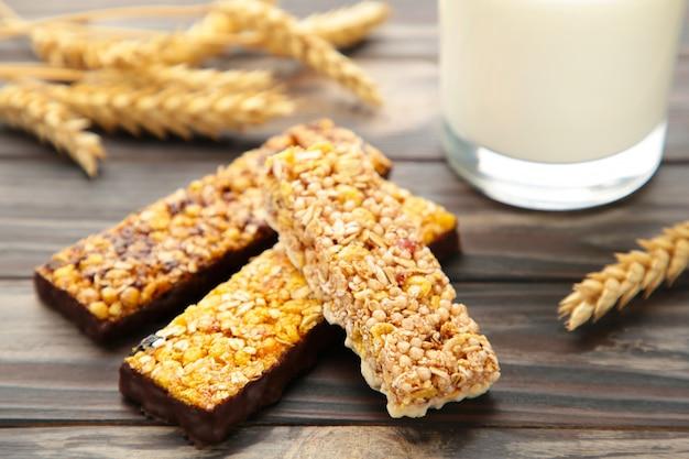 Sana colazione con barrette di cereali e latte sul tavolo di legno marrone.