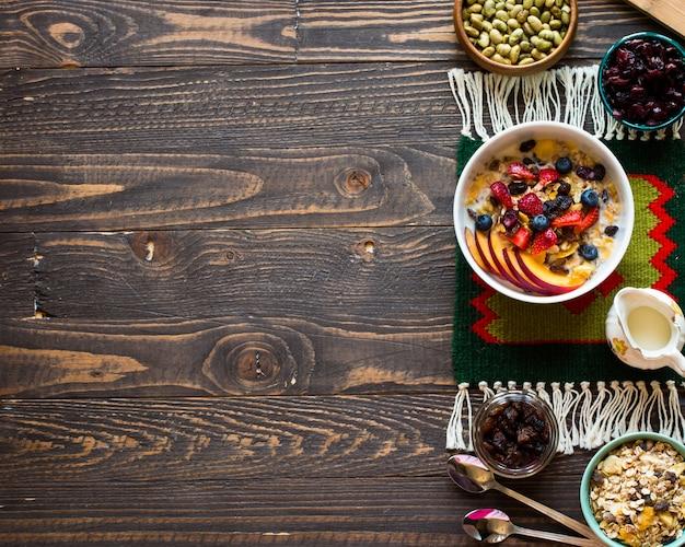 Sana colazione con latte, muesli e frutta, su uno sfondo di legno.