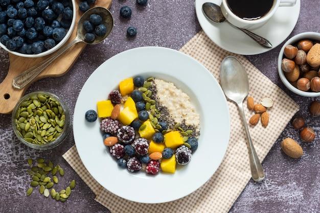 Sana colazione con porridge di farina d'avena con frutta e caffè