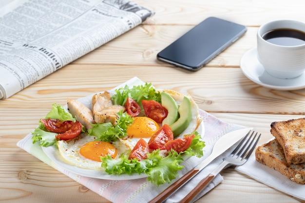 Sana colazione d'affari in stile europeo o americano con uova fritte, verdure ed erbe. avvicinamento