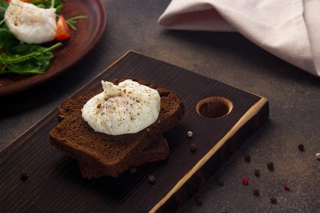 Sana colazione di pane tostato con uovo in camicia, pomodori su un tavolo scuro
