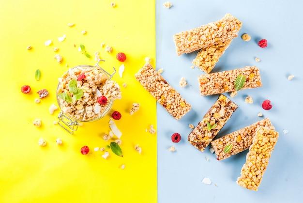 Sana colazione e spuntino, muesli fatto in casa con lamponi freschi e noci in barattolo e barrette di cereali, su luminoso giallo e blu senza cuciture