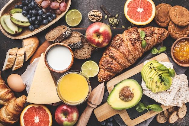 Sana colazione equilibrata su uno sfondo scuro. muesli, latte, succo di frutta, croissant, formaggio, biscotti.