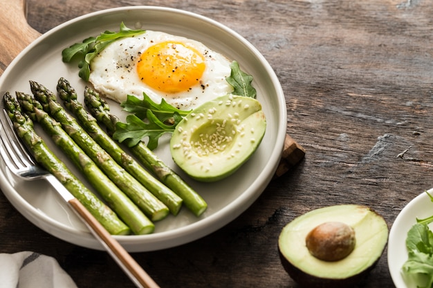Sana colazione fatta in casa con asparagi, uovo fritto, avocado e rucola. concetto di cibo sano quarantena. dieta cheto