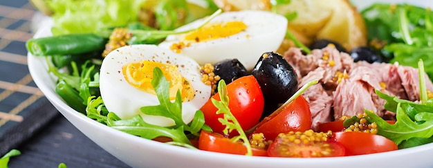 Sana e abbondante insalata di tonno, fagiolini, pomodori, uova, patate, olive nere close-up in una ciotola sul tavolo. insalta di nicoise. cucina francese. bandiera
