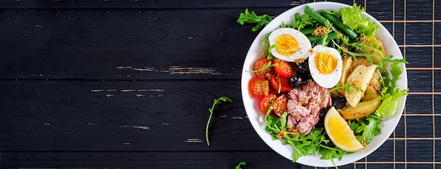 Sana e abbondante insalata di tonno, fagiolini, pomodori, uova, patate, olive nere close-up in una ciotola sul tavolo. insalta di nicoise. cucina francese. vista dall'alto. banner. disteso