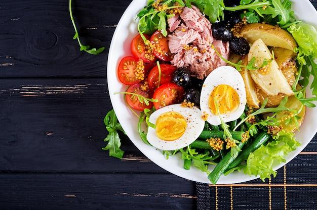 Sana e abbondante insalata di tonno, fagiolini, pomodori, uova, patate, olive nere close-up in una ciotola sul tavolo. insalta di nicoise. cucina francese. vista dall'alto. disteso