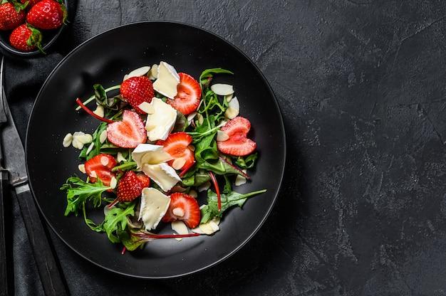 Sana e deliziosa insalata con camembert, fragole, noci, bietole e rucola. sfondo nero. vista dall'alto. copia spazio