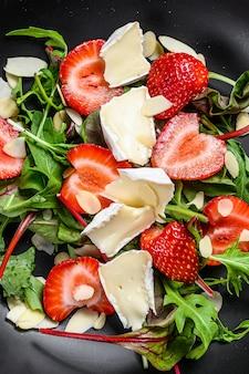 Sana e deliziosa insalata con camembert, fragole, noci, bietole e rucola. sfondo nero. vista dall'alto