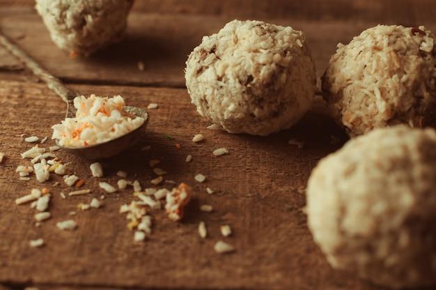 Sana energia al cioccolato morde con noci, datteri, scaglie di cocco su un tavolo di legno.
