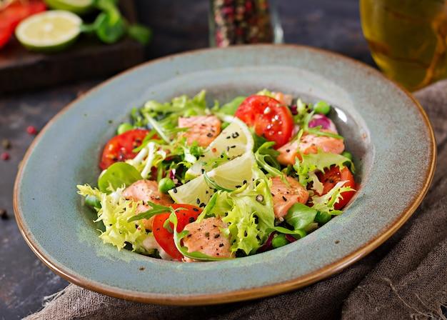 Sana insalata con pesce. salmone al forno, pomodori, lime e lattuga. cena salutare.