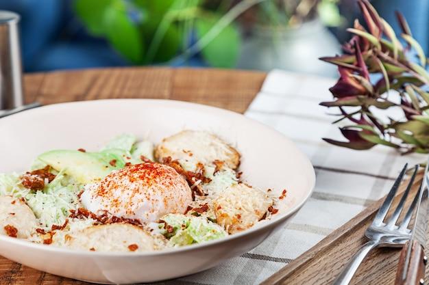 Sana insalata con petto di pollo al forno, uovo in camicia, lattuga, formaggio, avocado