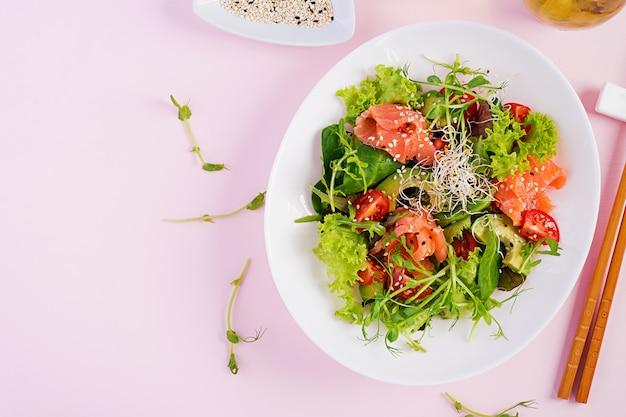 Sana insalata con verdure fresche, pomodori, avocado, rucola, semi e salmone