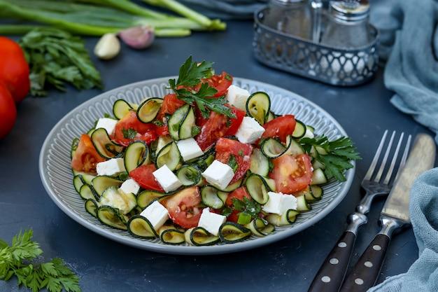 Sana insalata con zucchine, pomodori e feta, condita con olio d'oliva in un piatto su uno sfondo scuro, orientamento orizzontale