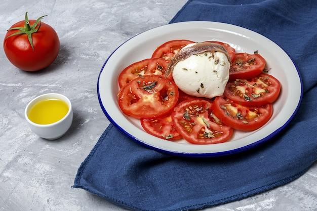 Sana insalata di pomodori fatta in casa con mozzarella, acciughe e origano