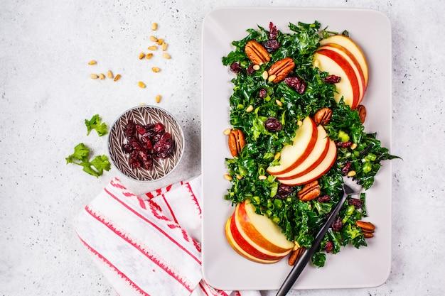 Sana insalata vegana con mela, mirtillo, cavolo e noci pecan in un piatto rettangolare, vista dall'alto.