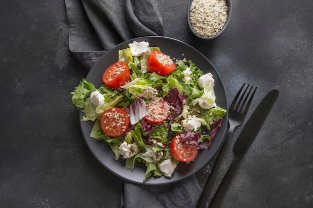 Sana insalata vegana nel piatto nero con pomodoro fresco, verdure, semi di canapa per mangiare pulito. vista dall'alto.