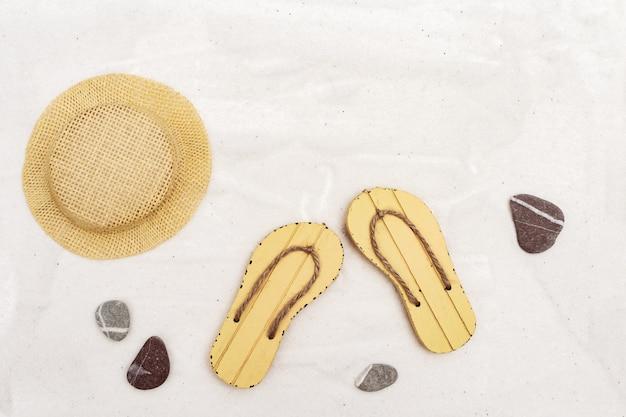Sandali da spiaggia e cappello di paglia su fondo di sabbia chiara. accessori da spiaggia. disteso. copia spazio.