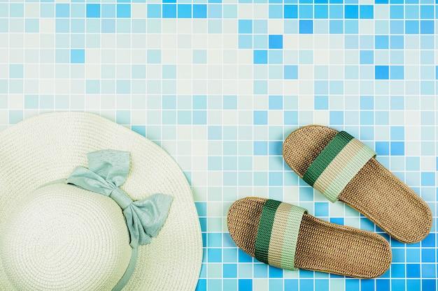 Sandali e un cappello da spiaggia su piastrelle di ceramica blu in piscina. - concetto di vacanze estive.
