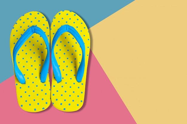 Sandali gialli su sfondo di colore rosa e blu, foto piatta laici