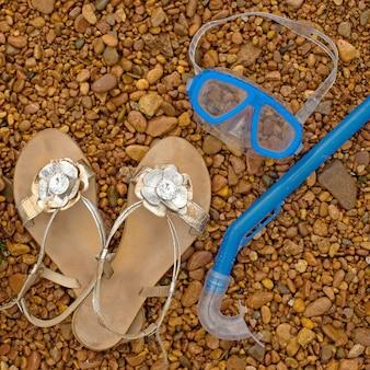 Sandali gonfiabili per cerbottoni, maschera subacquea, boccaglio sulla spiaggia.