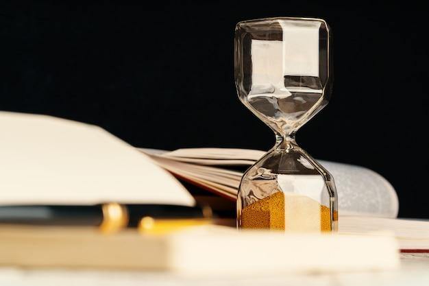 Sandglass sulla tavola di legno con la fine del libro aperto su